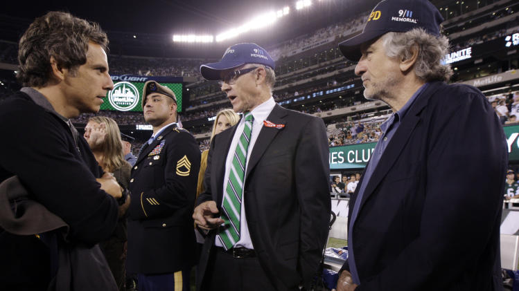 CORRECTS SPELLING OF DENIRO - Actors Ben Stiller, left and Robert DeNiro, right, speak with New York Jets owner Woody Johnson before an NFL football game between the Dallas Cowboys and New York Jets, Sunday, Sept. 11, 2011, in East Rutherford, N.J. In the background is Medal of Honor recipient Army Ranger Leroy Petry, of New Mexico. (AP Photo/Julio Cortez)