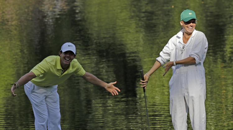 Rory McIlroy, of Northern Ireland, and tennis player Caroline Wozniacki react to applause on the ninth hole of the par three competition before the Masters golf tournament Wednesday, April 10, 2013, in Augusta, Ga. (AP Photo/David J. Phillip)