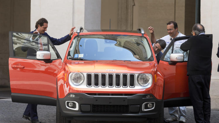 CEO of Chrysler and Fiat, Sergio Marchionne, right with back to camera, Fiat worker Ennio Meccia, second from right, and Fiat Chairman John Elkann, look at Italian Premier Matteo Renzi, third from right, entering in the 2015 Jeep Renegade during its presentation at Chigi palace, Premier's office, in Rome, Friday, July 25, 2014. (AP Photo/Alessandra Tarantino)