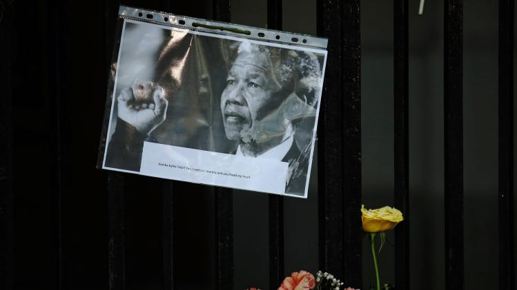 Flowers and tributes are left for former South African President Nelson Mandela at the South African High Commission in London