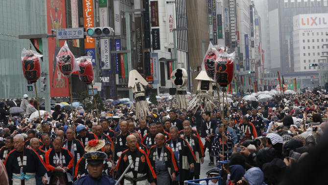 Members of a traditional firefighting preservation group along with Kabuki actors parade at Ginza shopping district in Tokyo, Wednesday, March 27, 2013. Some 60  actors paraded in the rain Wednesday to newly renovated Tokyo theatre ahead of its official opening.  (AP Photo/Shizuo Kambayashi)