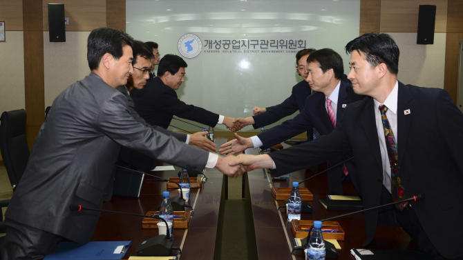 In this photo released by Unification Ministry, South Korean delegates, right, shake hands with their North Korean counterparts at the start of a meeting at Kaesong Industrial District Management Committee in Kaesong, North Korea, Wednesday, Sept. 11, 2013. Both Koreas agreed Wednesday to restart operations at a jointly run factory park that Pyongyang shut down in April during a torrent of threats, the latest sign of easing animosity between the rivals. (AP Photo/Unification Ministry)
