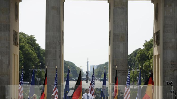 "President Barack Obama speaks in front of the iconic Brandenburg Gate in Berlin Germany, Wednesday, June 19, 2013. Obama spoke on the Gate's eastern side, across the old border from where President Ronald Reagan gave his unforgettable ""Mr. Gorbachev, tear down this Wall!"" speech in June 1997. This week also marks the 50th anniversary that President John F. Kennedy confronted Cold War tension in Wall-divided Berlin by telling residents, ""Ich bein ein Berliner."" From left are, German Chancellor Angela Merkel, and Berlin Mayor Klaus Wowereit. (AP Photo/Pablo Martinez Monsivais)"