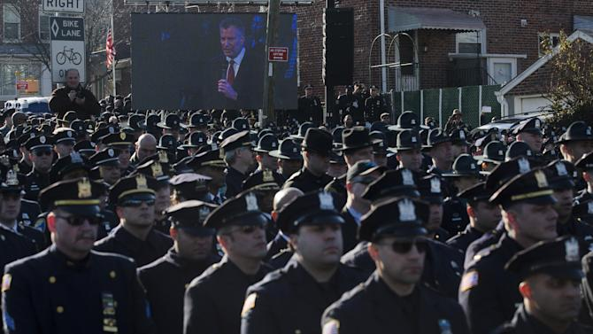 File-This Dec. 27, 2014, file photo shows police officers turning their backs as New York City Mayor Bill de Blasio speaks at the funeral of New York city police officer Rafael Ramos in the Glendale section of Queens, in New York. Mayor Bill de Blasio is winding down his first year in office, which saw success at fulfilling many of his liberal campaign promises. But the year ends with his young mayoralty facing its biggest crisis yet: an open rebellion from police officers who don't believe the mayor supports them. (AP Photo/John Minchillo)