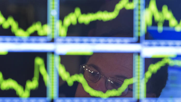 In this Monday, July 22, 2013, photo, Specialist Douglas Johnson is reflected in a screen at his post on the floor of the New York Stock Exchange. A mix of good and bad earnings reports from big companies kept the stock market treading water in early trading Tuesday, July 23, 2013. (AP Photo/Richard Drew)