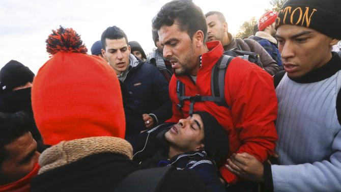 Migrants carry an unconscious man after they tried to run through a line of Macedonian police and cross the Greek-Macedonian border near the Greek village of Idomeni