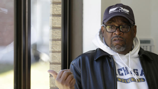 Michael Wofford, 59, points outside a doorway where a Reshad Riddle shot his father in a Sunday shooting that occurred at the Hiawatha Church of God in Christ Monday, April 1, 2013, in Ashtabula, Ohio. Police say Reshad Riddle killed his father, Richard Riddle, with a single shot from a handgun Sunday afternoon. (AP Photo/Tony Dejak)