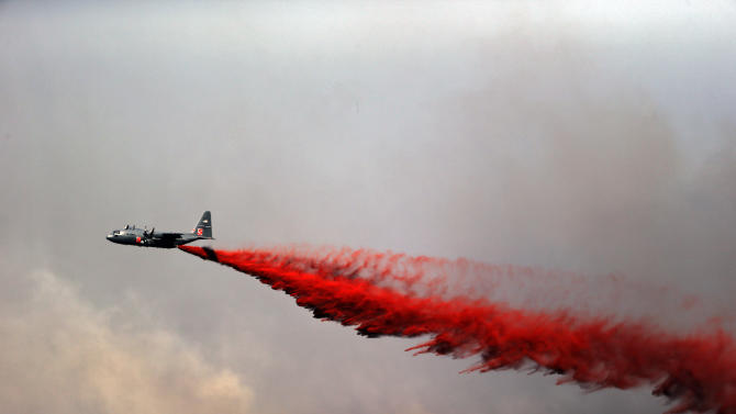 A U.S. Army C-130 makes a slurry drop on a wildfire in the Black Forest area north of Colorado Springs, Colo., on Wednesday, June 12, 2013. As many as 50 homes were destroyed by the fire on Tuesday. (AP Photo/Ed Andrieski)