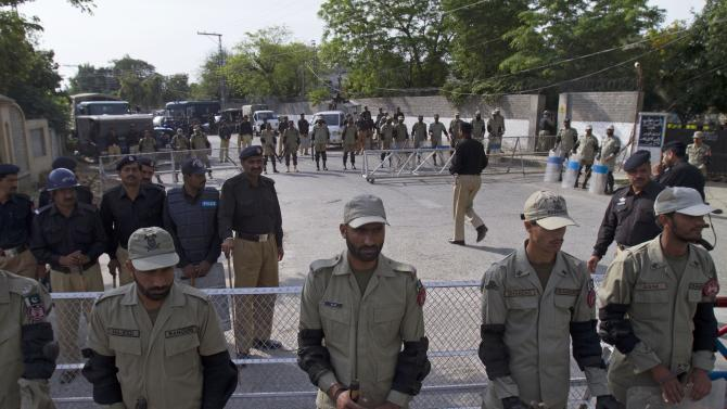 Paramilitary troops and police officers cordon off the vicinity of an anti-terrorism court, where Pakistan's former President and military ruler Pervez Musharraf is appearing in Rawalpindi, Pakistan, Tuesday, April 23, 2013. Musharraf appeared before anti-terrorism court over the assassination of former prime minister Benazir Bhutto's case, official said.  (AP Photo/Anjum Naveed)