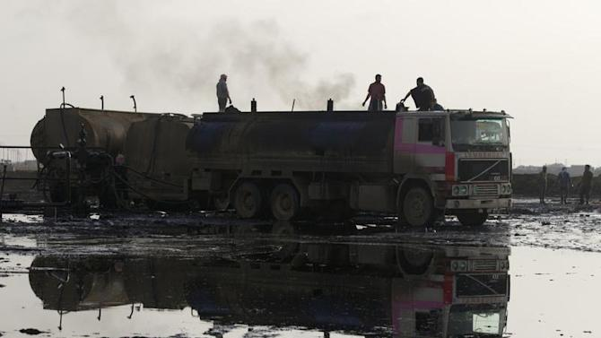 People stand on trucks near oil fields in Al-Rmelan, Qamshli province