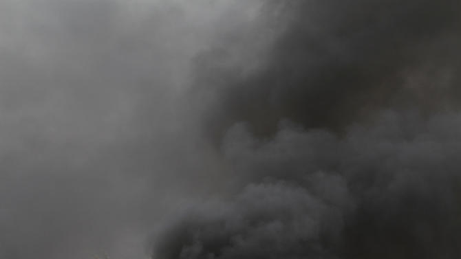 Tires set ablaze by Bahraini anti-government protesters fill the air with black smoke Sunday, April 22, 2012, in Jidhafs, Bahrain, just outside the capital of Manama. Security forces in Bahrain set up checkpoints and stationed armored vehicles in anti-government strongholds Sunday to confront possible protests coinciding with the Gulf nation's Formula One Grand Prix. (AP Photo/Hasan Jamali)