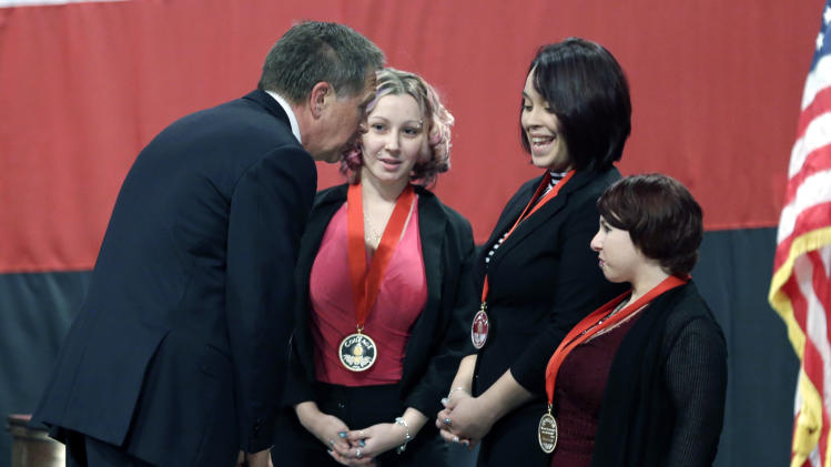Ohio Gov. John Kasich, from left, talks with Amanda Berry, Gina DeJesus and Michelle Knight after they received the Governor's Courage Award, during Kasich's State of the State address at the Performing Arts Center Monday, Feb. 24, 2014, in Medina, Ohio. The three women survived a decades-long captivity in Cleveland before being rescued in May when Berry pushed her way through a door to freedom. (AP Photo/Tony Dejak)
