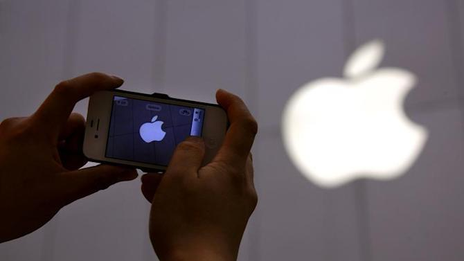 A man shows a photograph he took on his iPhone of an Apple store in Beijing