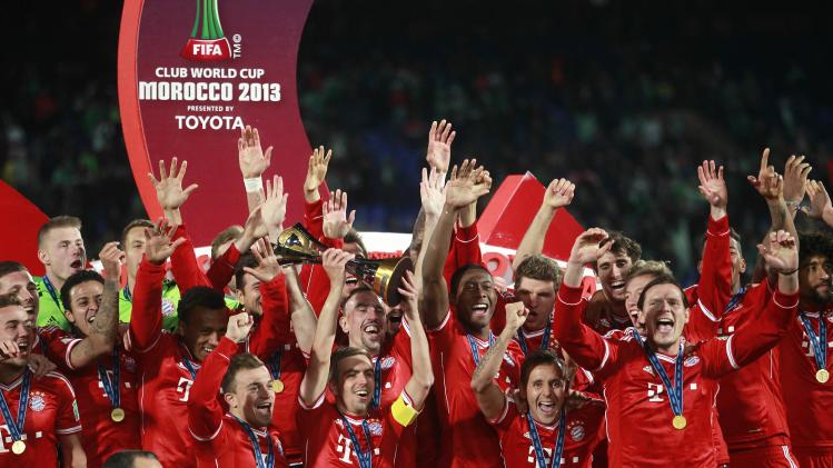 Philipp Lahm of Germany's Bayern Munich holds the trophy as he celebrates with his team mates after winning their 2013 FIFA Club World Cup final soccer match against Morocco's Raja Casablanca at Marrakech stadium
