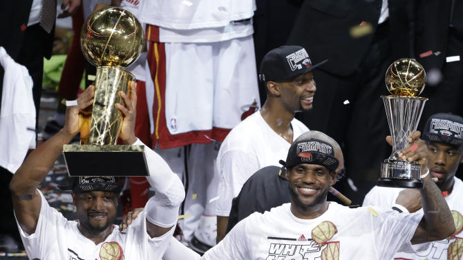 The Miami Heat's Dwyane Wade, left, holds the Larry O'Brien NBA Championship Trophy as LeBron James holds his Bill Russell NBA Finals Most Valuable Player Award after Game 7 of the NBA basketball championship against the San Antonio Spurs, Friday, June 21, 2013, in Miami. The Miami Heat defeated the San Antonio Spurs 95-88 to win their second straight NBA championship. (AP Photo/Wilfredo Lee)