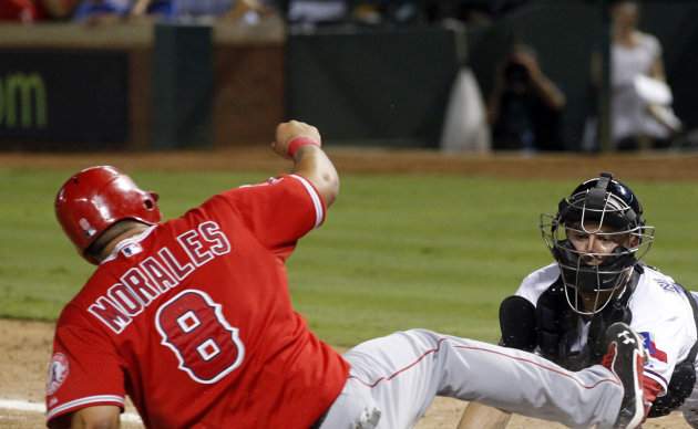 Los Angeles Angels' Kendrys Morales (8) is tagged out at home plate by Texas Rangers catcher Mike Napoli, right, while trying to score on a single by Maicer Izturis during the ninth inning of a baseball game Wednesday, Aug. 1, 2012, in Arlington, Texas. (AP Photo/John F. Rhodes)