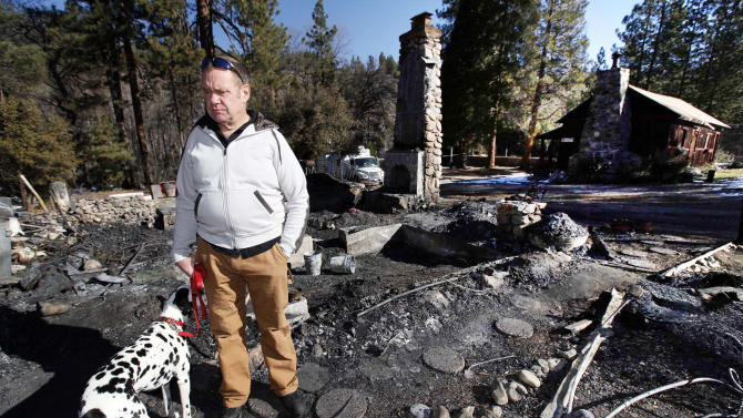 Rick Heltebrake with his dog Suni looks over the burned-out cabin where Christopher Dorner's remains were found after a police standoff Tuesday near Big Bear, Calif., Friday Feb. 15, 2013.   Heltebrake had been carjacked by Dorner. (AP Photo/Nick Ut)