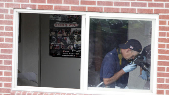 """FBI agents photograph the bedroom in the apartment of alleged gunman James Holmes with a poster titled """"Soldiers of Misfortune"""" Saturday, July 21, 2012 in Aurora, Colo. Authorities reported that 12 died and more than three dozen people were shot during an assault at a movie theatre midnight premiere of """"The Dark Knight Rises."""" (AP Photo/Alex Brandon)"""