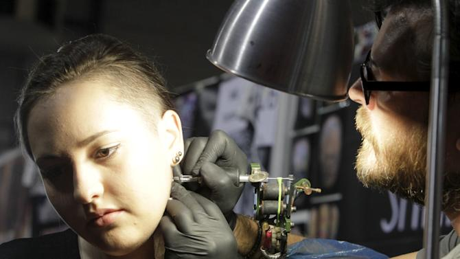An artist draws a tattoo on a woman's neck during a tattoo convention in Ljubljana