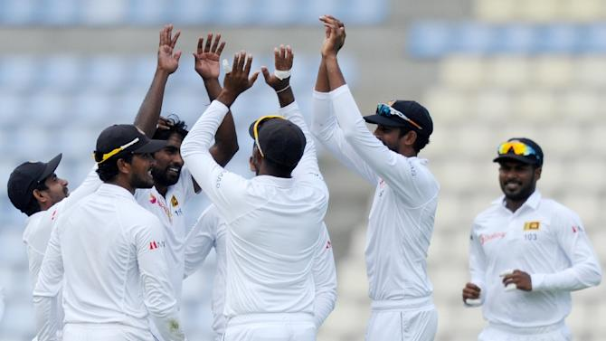 Sri Lanka celebrate the dismissal of Pakistan's Ahmed Shehzad during the second day of the third and final Test match on July 4, 2015