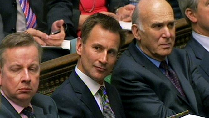 Britain's Culture Secretary Jeremy Hunt, center, looks on as Prime Minister David Cameron speeks during Prime Minister's Questions in the House of Commons, London Wednesday June 13, 2012. Britain's coalition government is split on whether to back a Conservative minister over the way he dealt with Rupert Murdoch's News Corp. The British media, including Press Association, say Deputy Prime Minister and Liberal Democrat leader Nick Clegg has asked his lawmakers to abstain on a vote Wednesday afternoon on whether Culture Secretary Jeremy Hunt should be investigated over how he dealt with News Corp. as it was trying to take full control of a satellite broadcaster in which News Corp. already holds a 39 percent stake.   (AP Photo/PA Wire)  UNITED KINGDOM OUT