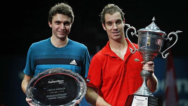 Thailand Open tennis tournament men's singles winner Richard Gasquet (R) of France lifts up his trophy next to runner-up compatriot Gilles Simon in Bangkok