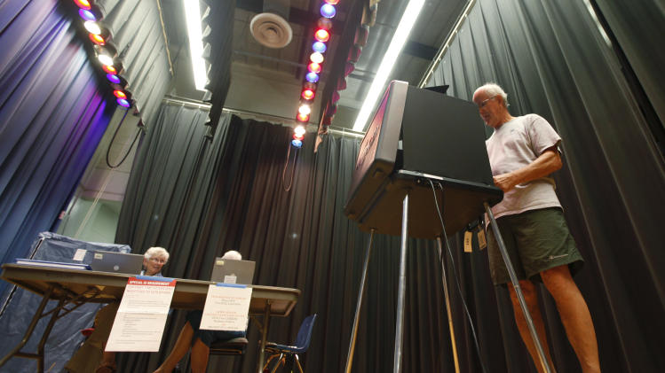 Jim Teachey votes in the Republican primary at a school precinct in Richmond, Va., Tuesday, June 12, 2012.  Turnout was low in the precinct that is set up in the auditorium stage of a local school.  (AP Photo/Steve Helber)