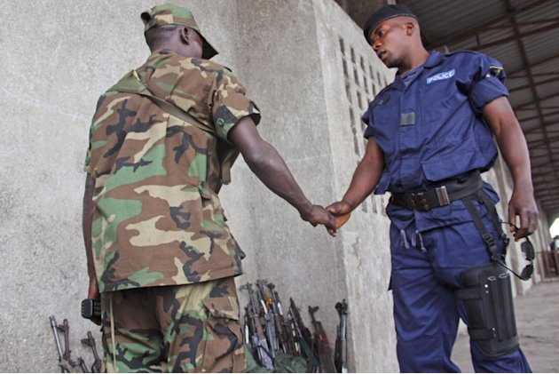 A Congo government policeman shake hands with an M23 rebel, after he and other policemen handed their weapons in to M23 rebels during a M23 rally in Goma, Congo, Wednesday, Nov. 21, 2012. A rebel grou