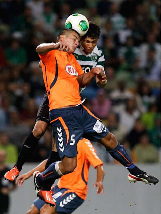 Sporting's Montero, from Colombia, right, heads the ball with Setubal's Javier Cohene, from Paraguay, during their Portuguese league soccer match Saturday, Oct. 5 2013, at Sporting's Alvalade stadium