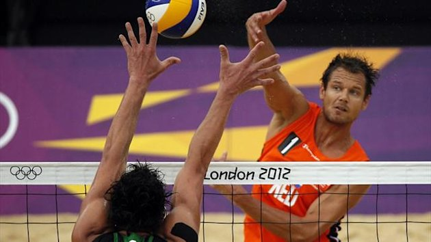 Reinder Nummerdor (R) of the Netherlands spikes the ball against Germany's Jonathan Erdmann during their men's preliminary round beach volleyball match at the London 2012 Olympic Games (Reuters)