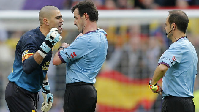 Barcelona's goalkeeper Victor Valdes, left argues with the referee after the final whistle during a Spanish La Liga soccer match against Real Madrid at the Santiago Bernabeu stadium in Madrid, Saturday March 2, 2013. Valdes was expelled. Real Madrid won the game 2-1. (AP Photo/Paul White)
