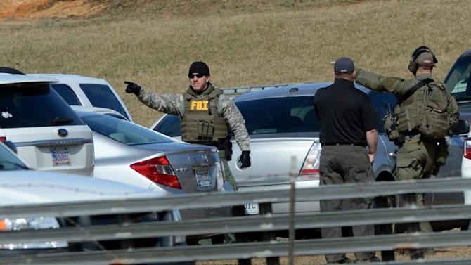Law enforcement officials continue to work the scene of an ongoing hostage crisis in Midland City, Ala., Friday, Feb. 1, 2013. Local, state and federal officers wait out a man accused of shooting and killing a school bus driver, then snatching a 5-year-old child. Suspect Jimmy Lee Dykes has been holed up in a bunker on his property with the child since the late afternoon shooting on Tuesday, Jan. 29, 2013. (AP Photo/al.com, Julie Bennett)