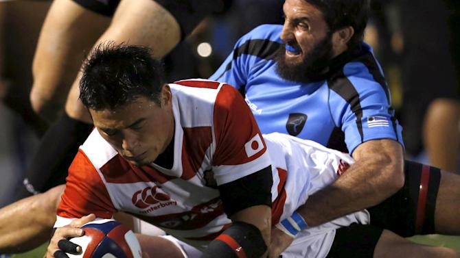 Japan's Ayumu Goromaru is tackled by Uruguay's Santiago Gibernau as he dives to score a try  during their international rugby test match in Tokyo