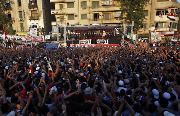Egyptians wave to Egypt's President-elect, Mohammed Morsi, upon his arrival to give a speech at Tahrir Square in Cairo, Egypt, Friday, June 29, 2012. In front of tens of thousands of cheering supporte