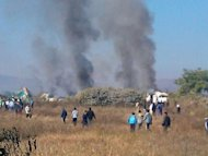 <p>This photo, taken with a camera phone on December 25, 2012, shows smoke rising from the scene of an Air Bagan passenger plane crash near Heho airport in Myanmar's eastern Shan state. The plane, carrying 65 passengers including foreign tourists, crash-landed, leaving two people dead and 11 others injured.</p>