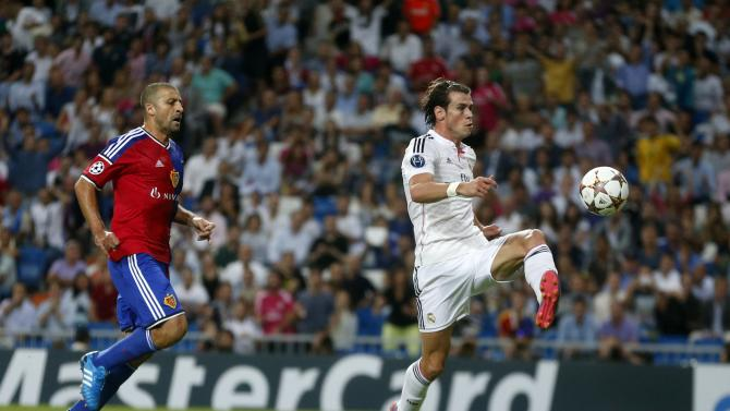Real Madrid's Gareth Bale kicks to score next to FC Basel's Walter Samuel during their Champions League soccer match at Santiago Bernabeu stadium in Madrid