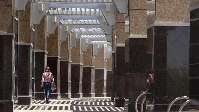 A visitor to the new North Las Vegas City Hall building walks down an outdoor corridor lined with marble columns, Thursday, June 21, 2012, in North Las Vegas, Nev. Despite its suburban trimmings, this blue-collar, family-oriented city outside Las Vegas is officially a disaster area. After five years of declining property taxes, massive layoffs and questionable spending choices, North Las Vegas city leaders declared a state of emergency earlier this month. (AP Photo/Julie Jacobson)