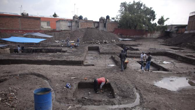 Workers clean an area of a recently discovered archeological site in Mexico City, Friday, July 13, 2012. According to Mexico's National Institute of Anthropology and History, INAH, the site is about 700 years old and is a neighborhood of the Tepaneca merchants. (AP Photo/Alexandre Meneghini)
