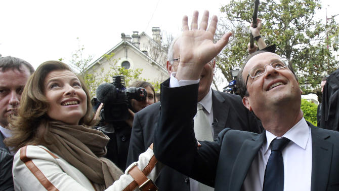 Socialist Party candidate for the presidential election Francois Hollande and his companion Valerie Trierweiler wave as he tours through villages near Tulle, central France, after voting in the second round of the presidential elections, Sunday, May 6, 2012.  (AP Photo/Bob Edme)