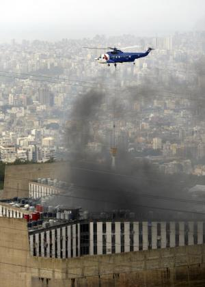 FILE - In this April 5, 2011, file photo, A rescue helicopter extinguishes the fire as smoke billows from the compound of the central Roumieh prison, where inmates have been rioting for several days, in Roumieh east of Beirut, Lebanon. Five inmates, of which some belong to al-Qaida-inspired Fatah Islam group, fled the prison on Saturday Aug. 13, 2011. Troops are conducing search operations around the compound. (AP Photo/Bilal Hussein, File)