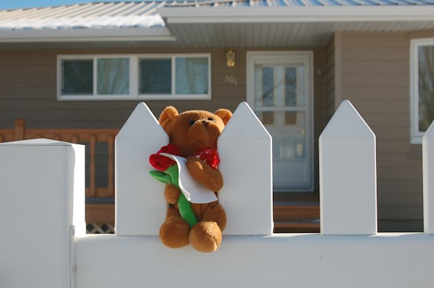 A stuffed bear is placed on a white picket fence on Monday, Nov. 19, 2012 in New Town, N.D. Authorities say  a woman and her three grandchildren were murdered in in the home on Sunday, Nov. 18, 2012. 