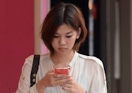 A Thai woman uses a mobile phone at a shopping mall in Bangkok. After years of delays, Thailand's top three mobile telephone operators will bid next week for licences to provide third-generation (3G) services in the kingdom, regulators said Tuesday
