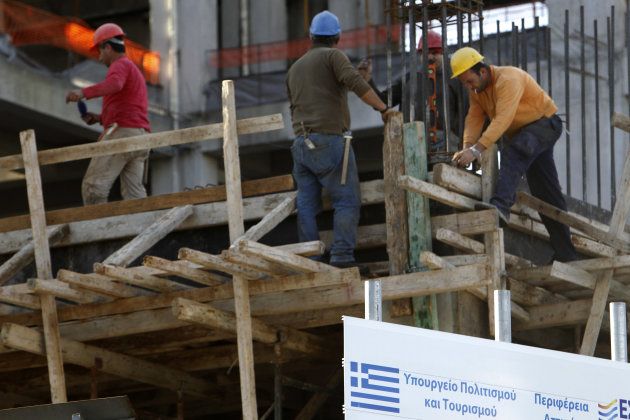 "Workers are seen on a building under construction behind a sing with a Greek flag which reads ""Greek Culture Ministry"" in Athens on Thursday, Nov. 8, 2012. Figures Thursday showed unemployment figures"