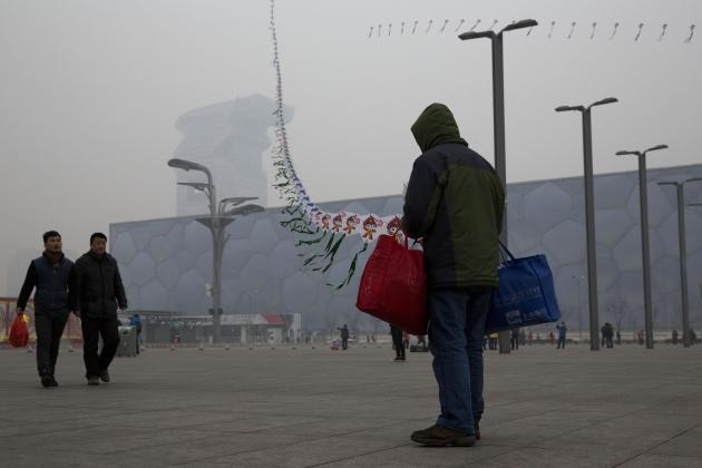 In this picture taken Sunday, Feb. 23, 2014, a street vendor flies kites printed with the Beijing Olympic games mascot image near the Water Cube aquatic center in Beijing, China. The Water Cube _ wher