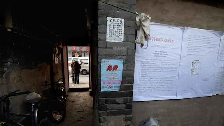 In this photo taken on Dec. 26, 2012, people chat outside a Hutong home as a demolition notice is placed on the wall near the historical Drum and Bell Tower in Beijing. The district government wants to demolish these dwellings, move their occupants to bigger apartments farther from the city center and redevelop a square in 18th century Qing Dynasty fashion. (AP Photo/Andy Wong)