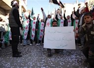 A man holds a placard as demonstrators protesting against Syria's President Bashar al-Assad gather during a march through the streets after Friday prayers in Baba Amro in Homs
