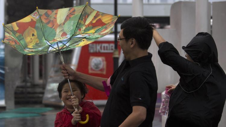 A child holds an inside-out umbrella broken due to strong winds before Typhoon Usagi is expected to make landfall, in Hong Kong