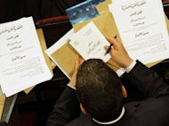 A newly-elected Syrian MP looks at papers including a copy of the country&#39;s new constitution and the agenda for the first officail session of the new parliament in Damascus