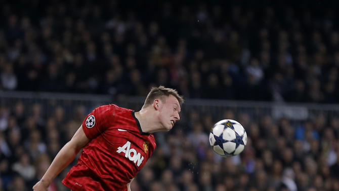 Real Madrid's Angel Di Maria from Argentina duels for the ball with Manchester United's Jonny Evans, up, during their Champions League round of 16 first leg soccer match at the Santiago Bernabeu stadium in Madrid, Wednesday Feb. 13, 2013. (AP Photo/Daniel Ochoa de Olza)