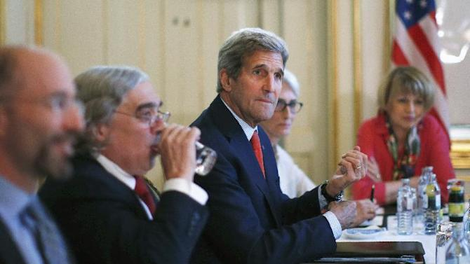 "U.S. Secretary of State John Kerry, centre, meets with Iranian Foreign Minister Mohammad Javad Zarif in Vienna, Austria, Friday July 3, 2015.  Iran has committed to implementing the IAEA's ""additional protocol"" for inspections and monitoring as part of an accord, but the rules don't guarantee international monitors can enter any facility including sensitive military sites, so making it difficult to investigate allegations of secret work on nuclear weapons. (Carlos Barria/Pool via AP)"